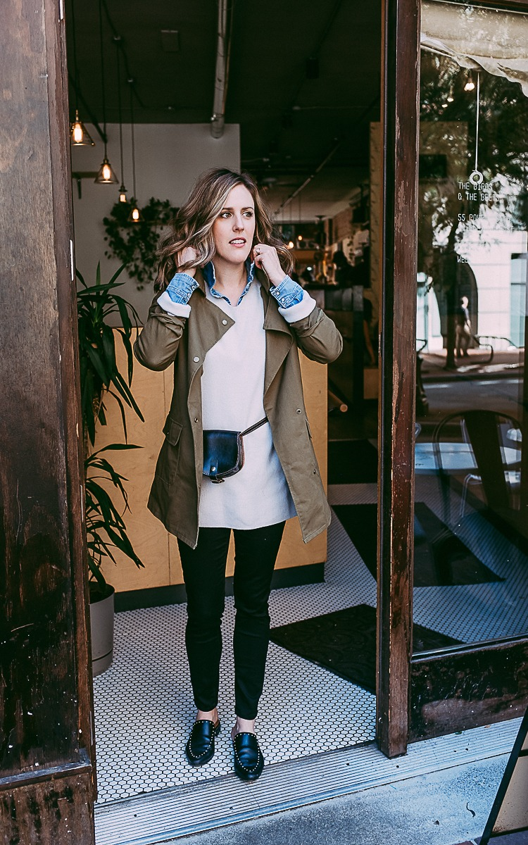 Fall layers with a green jacket, oversized sweater, jean shirt and fanny pack