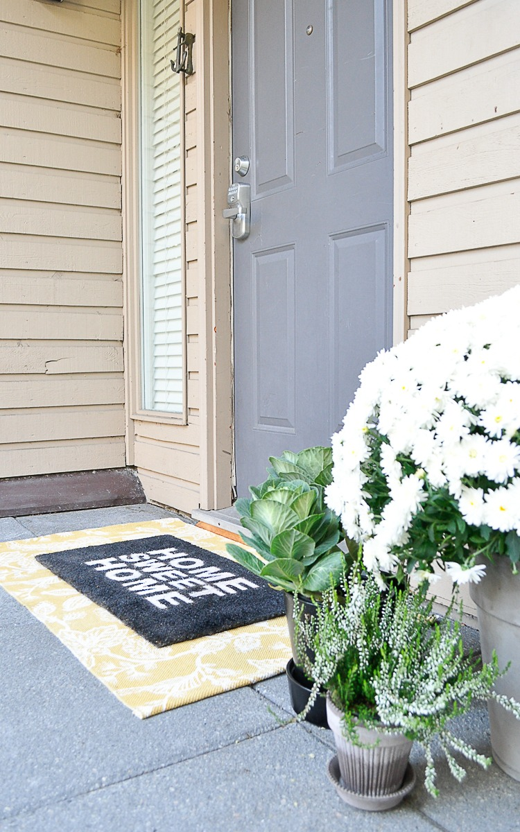 Layered front door rugs and fall greenery to refresh the front door.