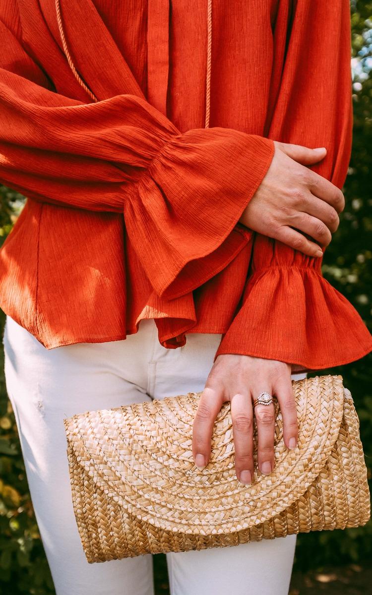 Straw clutch and orange shirt