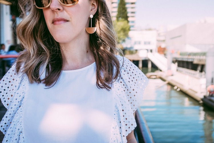 white eyelet blouse and gold accessories